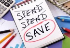 The word Save circled in red below a list of spending written on a notepad surrounded by pencils graphs books and calculator. Spending and saving concept.